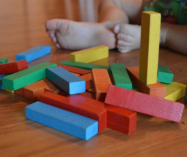 Enfant assis au milieu d'un tas de brique pour jouer
