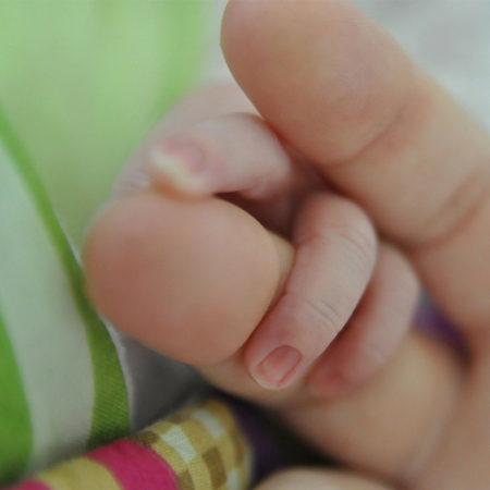 Main d'une mère qui tient la main de son bébé