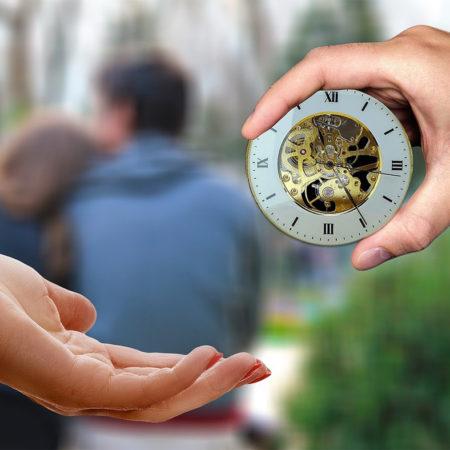 Couple amoureux en arrière plan, deux main qui se donne une horloge